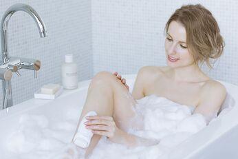 Frau epiliert in der Badewanne