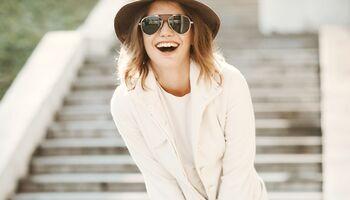 Lachende Frau in weißem Modetrend